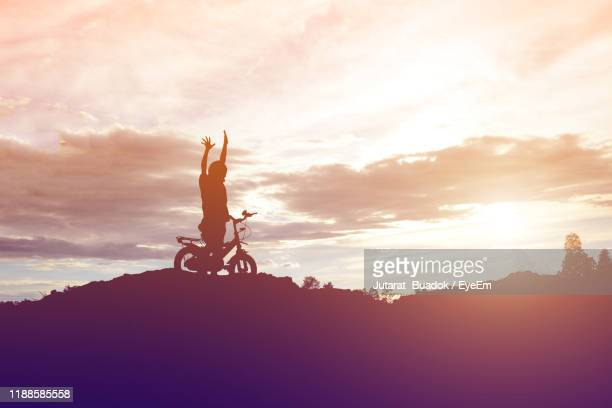 silhouette boy with arms raised standing with bicycle on land against sky during sunset - 8 9 anni foto e immagini stock
