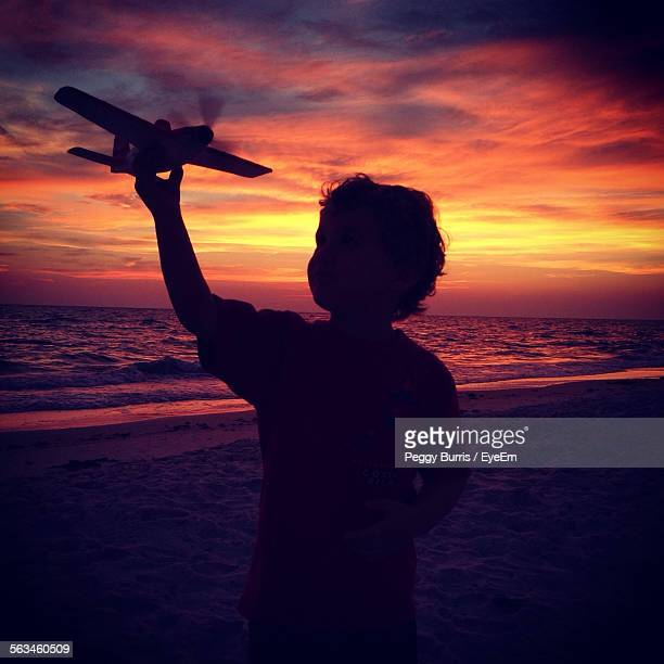 Silhouette Boy With Toy Airplane On Beach At Sunset