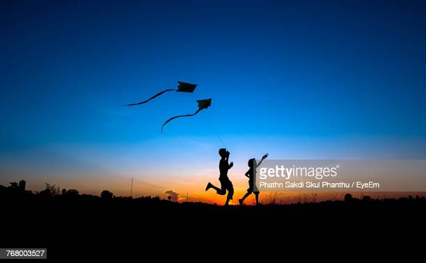 silhouette boys flying kite while running on field against blue sky during sunset - kite stock pictures, royalty-free photos & images