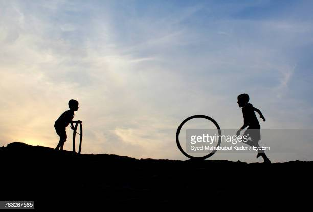 silhouette boys playing with tires against sky - bangladesh nature stock photos and pictures