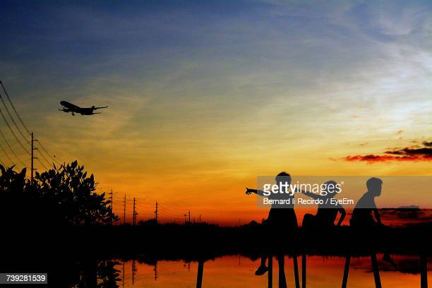 Silhouette Boys Pointing At Airplane Against Sky During Sunset