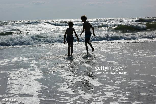 Silhouette Boys Running Towards Shore On Sunny Day