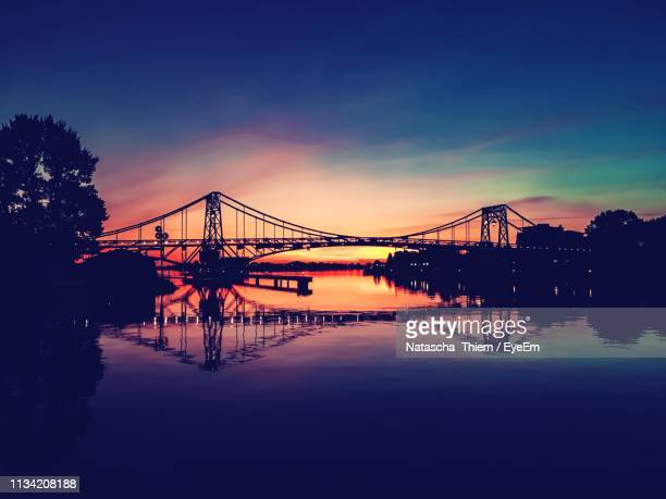 silhouette bridge over river against sky at sunset - thiem stock pictures, royalty-free photos & images