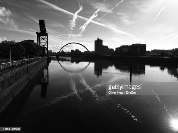 silhouette bridge over river against sky at sunset - govan stock pictures, royalty-free photos & images