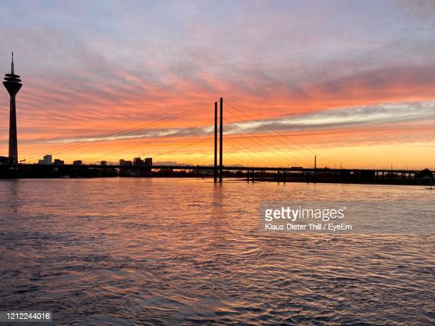 silhouette bridge over river against sky during sunset - klaus-dieter thill stock-fotos und bilder