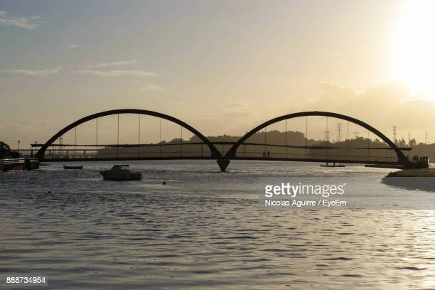 Silhouette Bridge Over River In City Against Sky