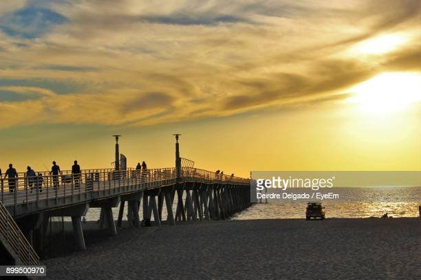 silhouette bridge over sea against cloudy sky - hermosa beach stock pictures, royalty-free photos & images