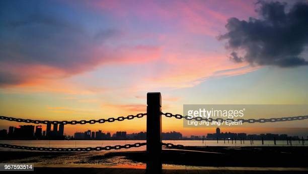 silhouette bridge over sea against dramatic sky during sunset - guangdong province stock photos and pictures