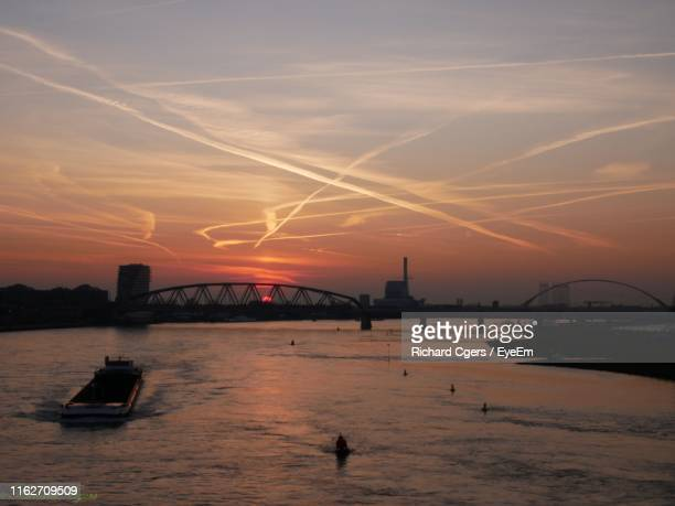 silhouette bridge over sea against sky during sunset - nijmegen stock pictures, royalty-free photos & images