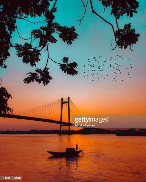 silhouette bridge over sea against sky during sunset - west bengal stock pictures, royalty-free photos & images