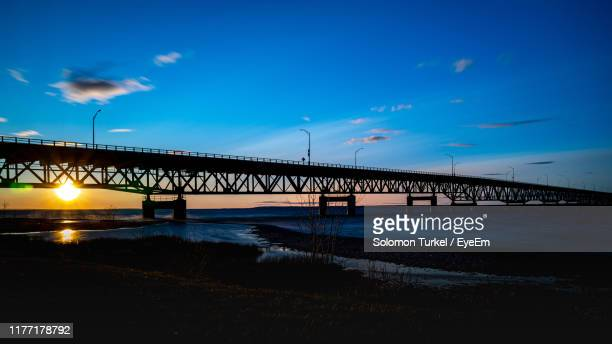 silhouette bridge over sea against sky during sunset - solomon turkel stock pictures, royalty-free photos & images