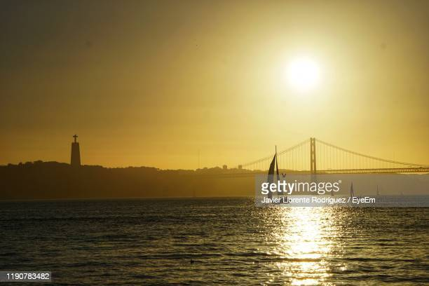 silhouette bridge over sea against sky during sunset - llorente stock pictures, royalty-free photos & images