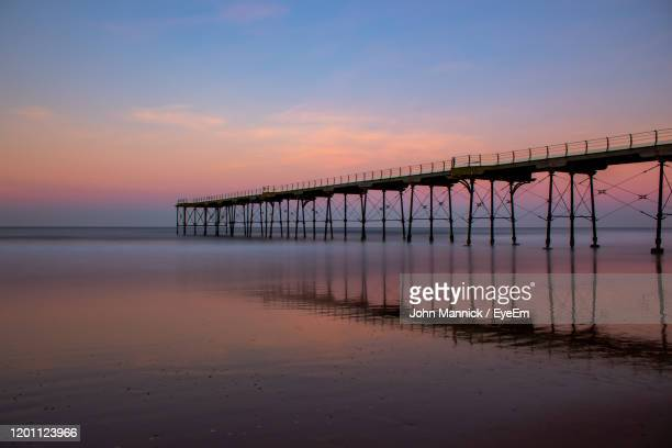 silhouette bridge over sea against sky during sunset - saltburn stock pictures, royalty-free photos & images