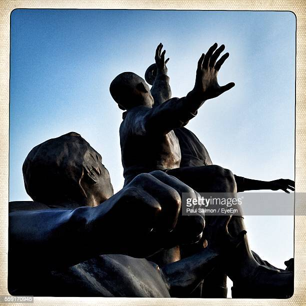 Silhouette Bronze Statue Of Rugby Against Sky