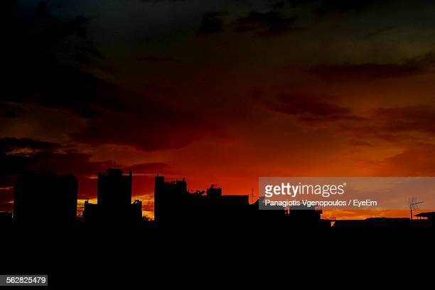 silhouette buildings against orange sky during sunset - vgenopoulos stock pictures, royalty-free photos & images