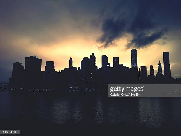 silhouette buildings against sky with water in foreground at night - new york skyline stock photos and pictures