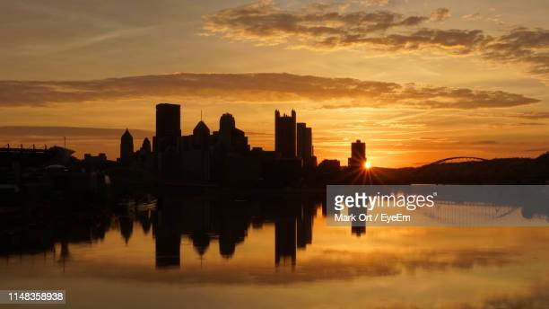 silhouette buildings by lake against sky during sunset - pittsburgh fotografías e imágenes de stock