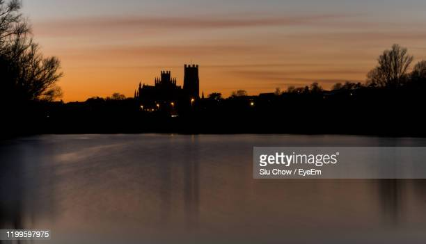 silhouette buildings by lake against sky during sunset - ケンブリッジシャー州 ストックフォトと画像