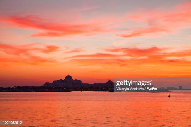 silhouette buildings by sea against dramatic sky during sunset - palace stock pictures, royalty-free photos & images