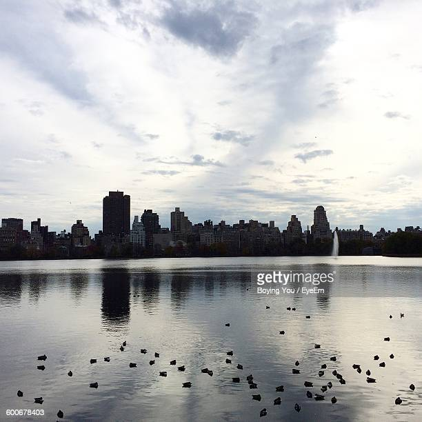 Silhouette Buildings In Distance With Reflection In River