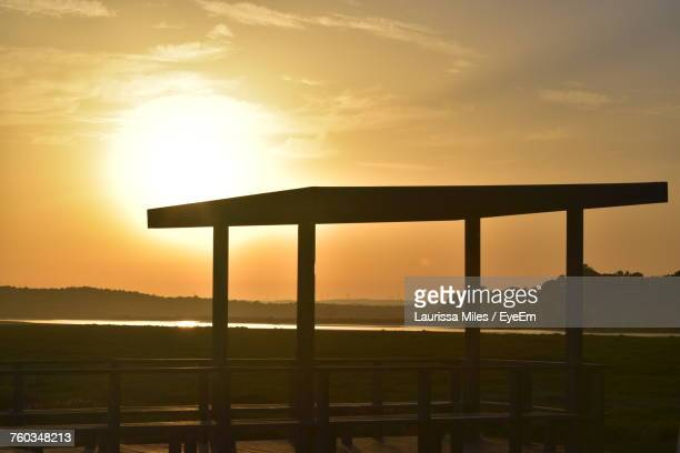Silhouette Built Structure On Field Against Sky During Sunset