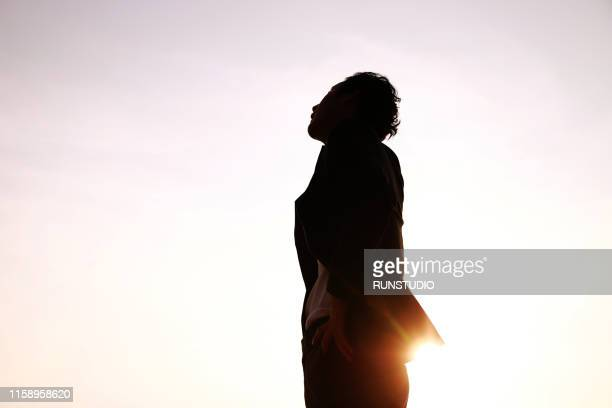 silhouette businessman looking up against sky at sunset - 期待 ストックフォトと画像