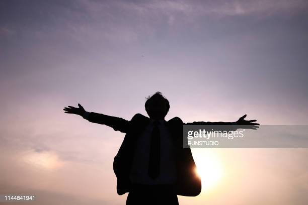 silhouette businessman stretching arms against sky at sunset - 朗らか ストックフォトと画像