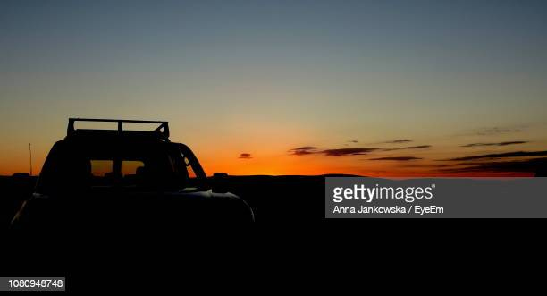 Silhouette Car On Field Against Sky During Sunset