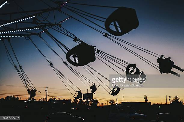 Silhouette Chain Swing Ride Against Sky During Sunset