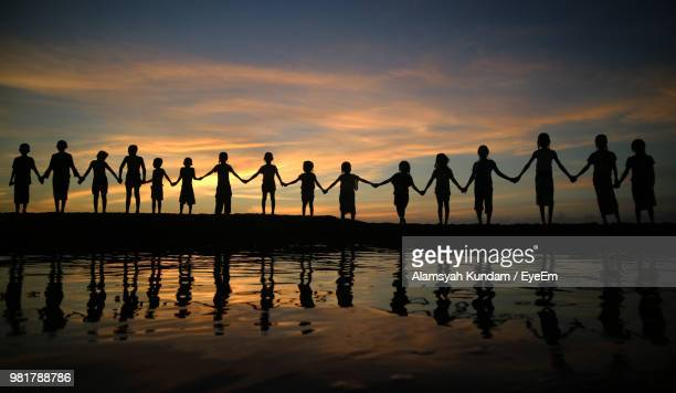 silhouette children holding hands while standing against sky during sunset - unity stock pictures, royalty-free photos & images