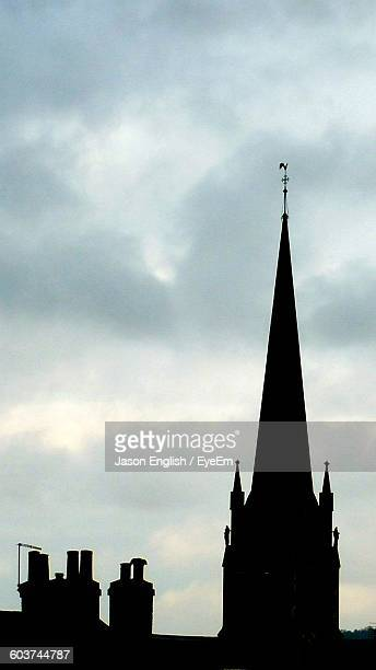 Silhouette Church Steeple With Chimney And Weather Vane Against Sky