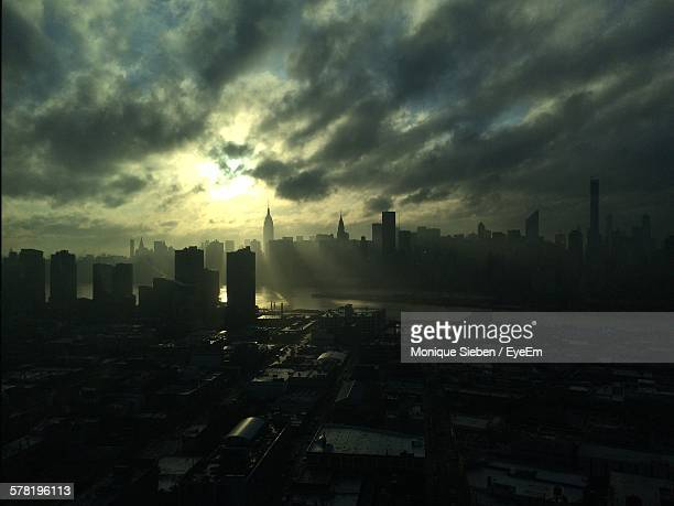 Silhouette Cityscape Against Cloudy Sky During Sunset