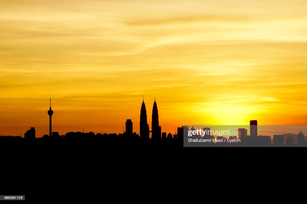 Silhouette Cityscape Against The Sky At Sunset : Stock Photo