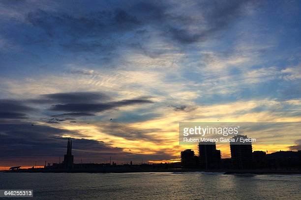 Silhouette Cityscape By Sea Against Sky During Sunset