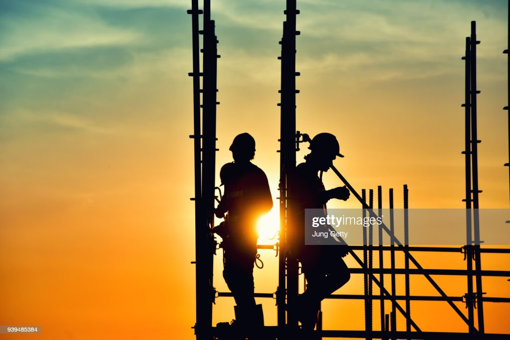 Silhouette civil site engineer and construction worker working on scaffolding in industrial construction during sunset sky background over time job : Foto de stock