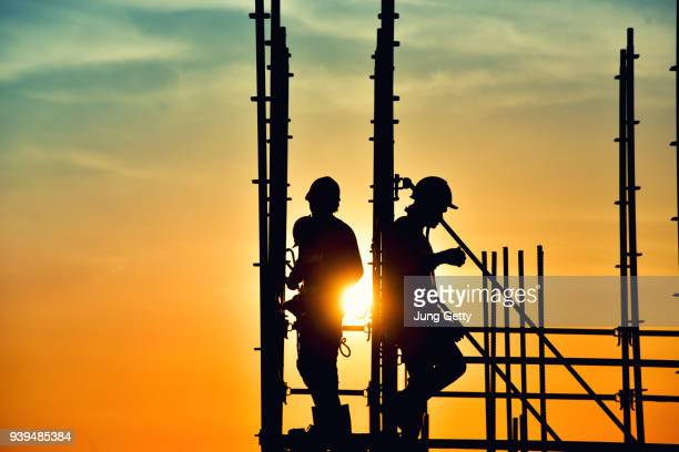 Silhouette civil site engineer and construction worker working on scaffolding in industrial construction during sunset sky background over time job