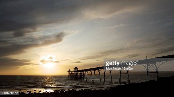 silhouette clevedon pier over sea against sky at sunset - clevedon pier stock pictures, royalty-free photos & images