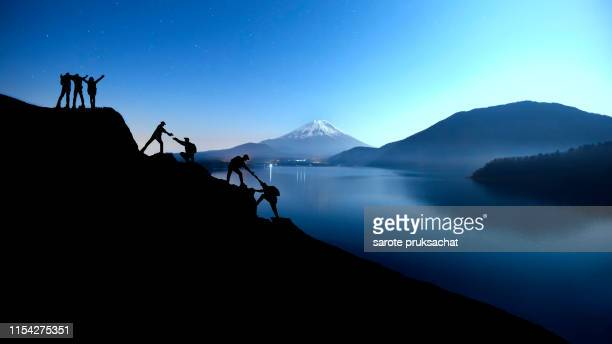silhouette climbing group friends walking to hike up mountain .teamwork , helps ,success, winner and leadership concept . - sportkleding stock pictures, royalty-free photos & images