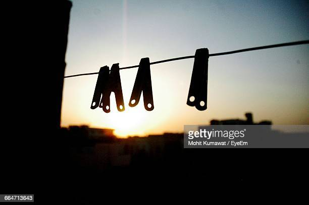 silhouette clothespins on rope against sky - 洗濯物 ストックフォトと画像