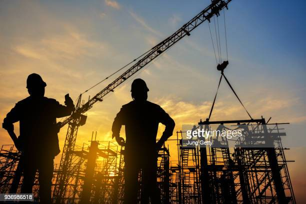 silhouette construction worker Concrete pouring during commercial concreting floors of building in construction site and Civil Engineer or Construction engineer inspec work