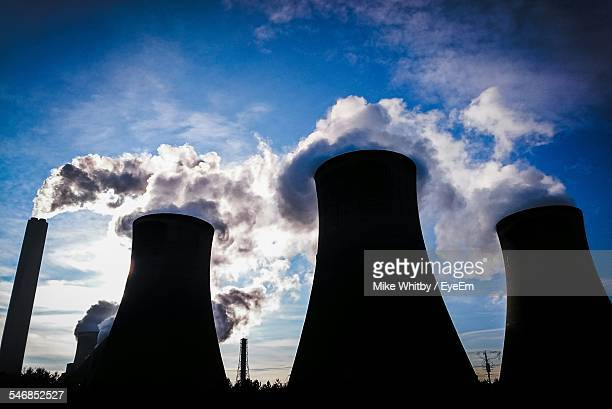 Silhouette Cooling Towers Emitting Smoke Against Sky