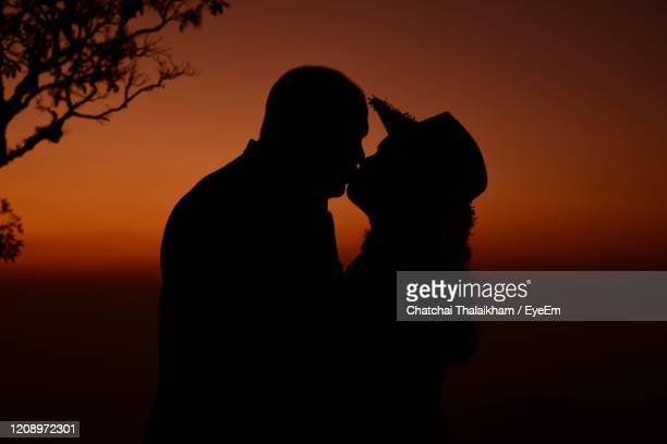 silhouette couple against orange sky during sunset - chatchai thalaikham stock pictures, royalty-free photos & images