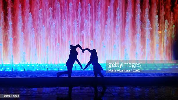Silhouette Couple Forming Heart Shape With Hands By Illuminated Fountain
