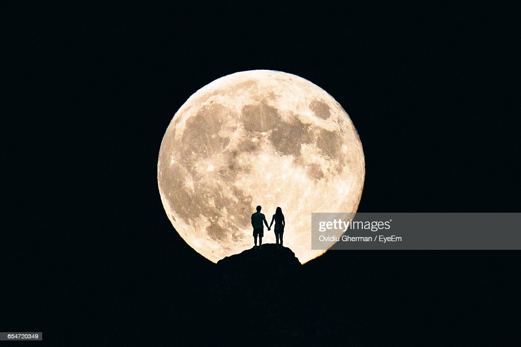 silhouette couple holding hands against moon at night