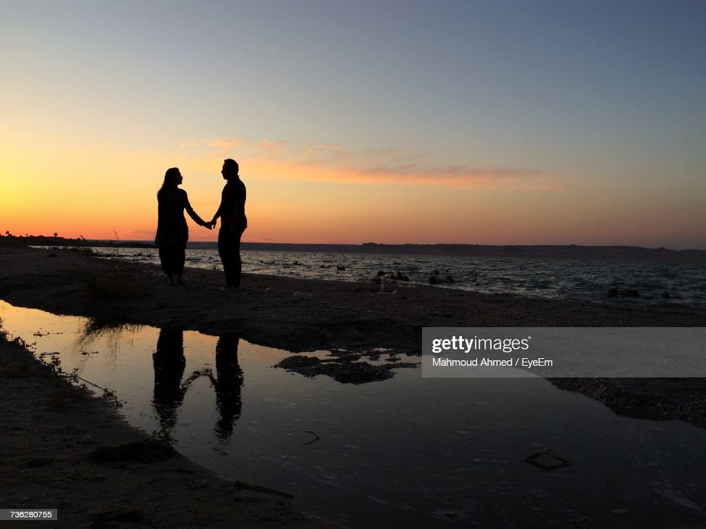 Silhouette Couple Holding Hands While Standing At Beach Against ... for Couple Holding Hands Silhouette Sunset  113lpg