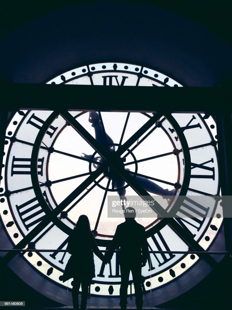 Silhouette Couple Holding Hands While Standing By Large Clock : Foto de stock