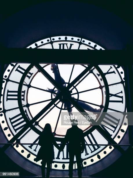 Silhouette Couple Holding Hands While Standing By Large Clock