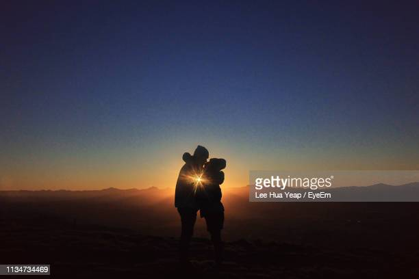 silhouette couple kissing against sky during sunset - blenheim new zealand stock pictures, royalty-free photos & images