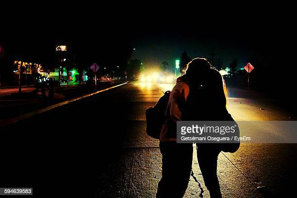 Silhouette Couple Kissing On Street At Night