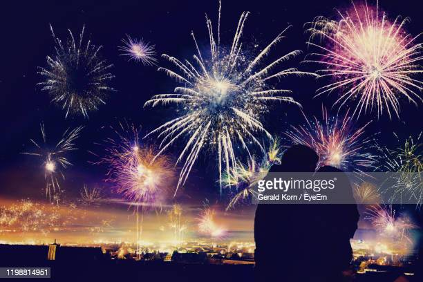 silhouette couple kissing while standing against firework display at night - kissing stock pictures, royalty-free photos & images